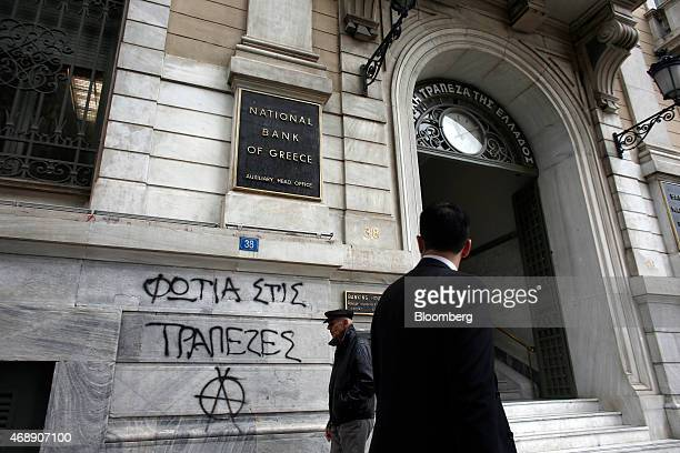Graffiti reading Burn the banks decorates the wall of the auxiliary head office of the National Bank of Greece SA in Athens Greece on Wednesday April...