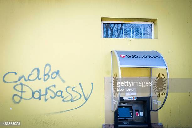 Graffiti reading Free Donbas sits on a wall beside an outofservice automated teller machine operated by UniCredit Bank AG with a hand written sign...