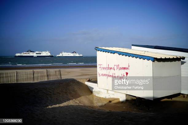 """Graffiti reading """"Freedom of Movement is everybody's right"""" covers a beach hut as a cross channel ferries arrive and depart the Calais Ferry terminal..."""