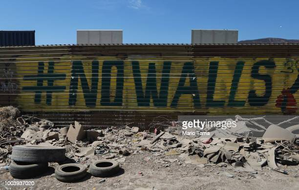 Graffiti reading 'No Walls' stands along the USMexico border fence with President Trump's border wall prototypes in the background on July 21 2018 in...