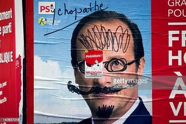 A graffiti reads 'Psychopath' on a campaign poster of Socialist Party candidate for the 2012 French presidential election Francois Hollande on April...