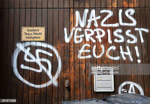 A graffiti showing a crossed out swastika and the lettering Nazis piss off is seen on a door of the regional branch of Germany's rightextremist NPD...