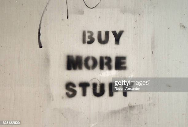 Graffiti stencilpainted on the back of a cluster mailbox in Aspen Colorado encourages people to 'Buy More Stuff'
