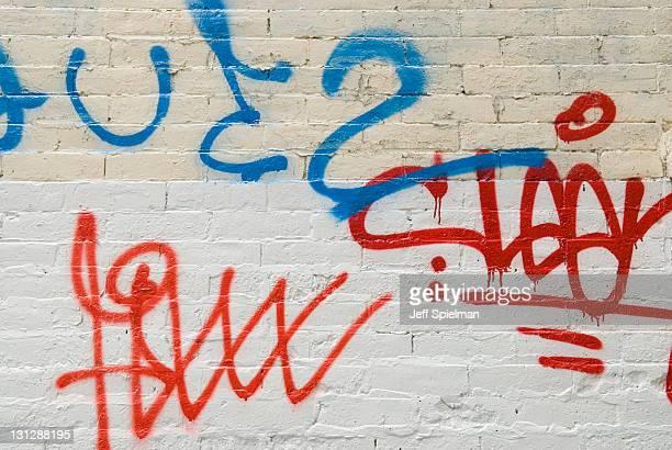 Graffiti Tags Spray Painted on a White Brick Wall