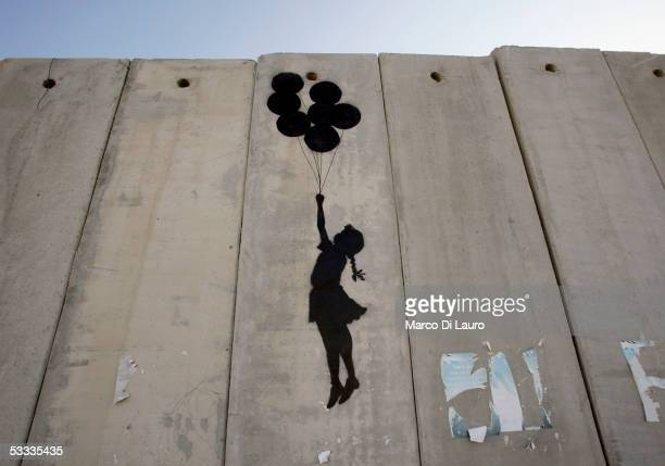 "Graffiti titled ""Balloon Debate"" made by the British guerrilla, graffiti artist Banksy, is seen on August 6, 2005 on Israel's highly controversial..."