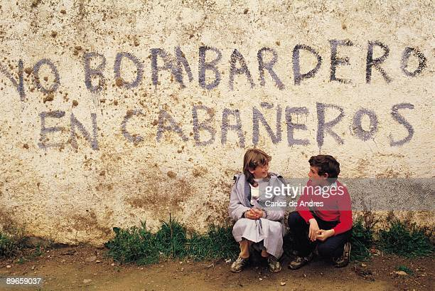 Graffity of protest Two children under a painting of protest against the creation of a shot field in the natural area of Cabaneros
