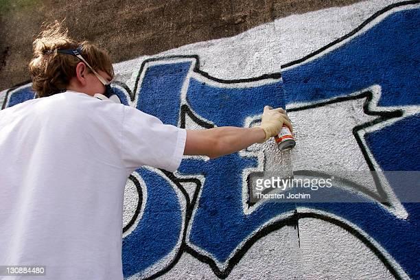 Graffity sprayer at work in Munich in railway underpass