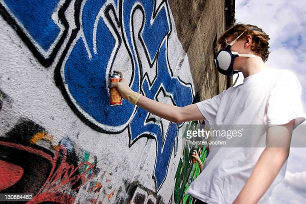 Graffity sprayer with breathing protection at work in Munich in railway underpass