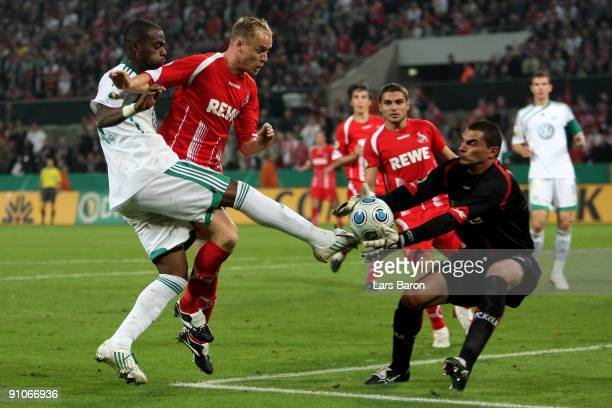 Grafite of Wolfsburg is challenged by Kevin McKenna and goalkeeper Faryd Mondragon of Koeln during the DFB Cup second round match between 1 FC Koeln...