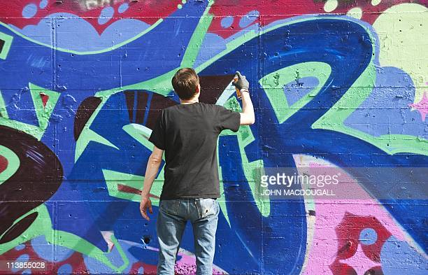 A grafitti artist works on a tag at the foot of the main tower topped by a radar dome of a former US National Security Agency run listening station...