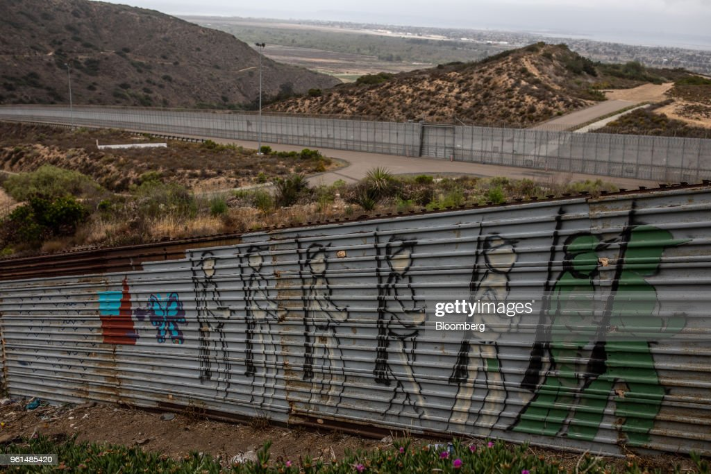Grafitti illustrating soldiers walking is displayed along a section of a U.S.-Mexico border wall in Tijuana, Mexico, on Monday, May 21, 2018. 'We won't care about threats of a wall,' National Regeneration Movement Presidential candidate Andres Manuel Lopez Obrador announced, assuring another rally crowd in Zacatecas, one of the states that sends the most migrants to the U.S., that with him in power, they'll achieve equal footing with their neighbors to the north. Photographer: Alejandro Cegarra/Bloomberg via Getty Images