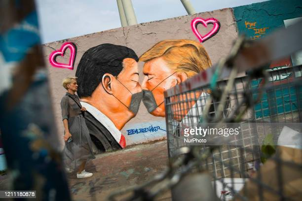 Grafitti of the artist Eme Freethinker representing US President Donald Trump and Chinese President Xi Jinping kissing while wearing protective masks...