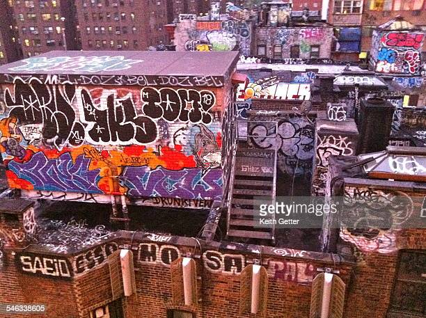 Grafitti on the top of brick tenement buildings in Chinatown Manhattan NYC as seen from the walkway of the Manhattan Bridge is a special place for...