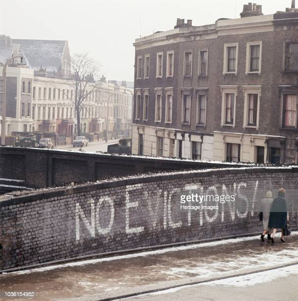 Grafton Road, Camden, London, c1960s. Two women walking past the graffiti No Evictions! on a railway bridge on Grafton Road. Much of the area was...