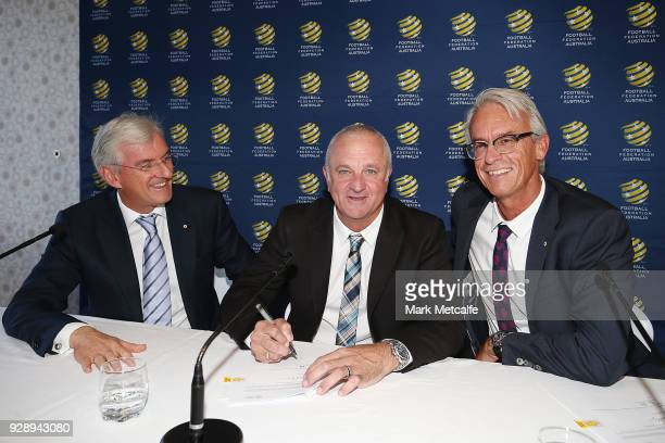Graham Arnold signs a contract alongside FFA Chairman Steven Lowy and FFA CEO David Gallop during a press conference announcing the succession plan...