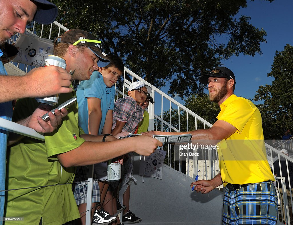 Graham DeLaet of Canada signs autographs for fans during the first round of the BMW Championship at Conway Farms Golf Club on September 12, 2013 in Lake Forest, Illinois.