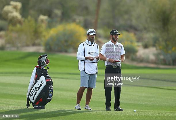 Graham DeLaet of Canada stands with his caddie prior to playing his third shot on the second hole during the first round of the World Golf...