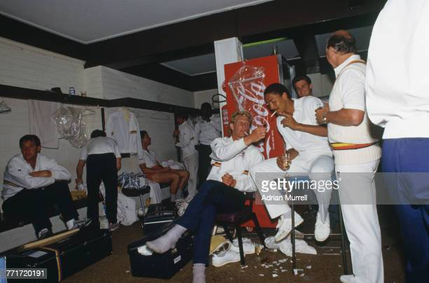 Graham Dilley lights a cigarette for Phil DeFreitas in the England dressing room after the team beat Australia by seven wickets in the 1st Test on...