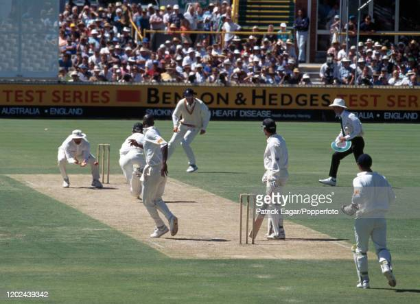 Graham Gooch of England catches the throw from teammate Chris Lewis to run out Craig McDermott of Australia closing Australia's 1st innings and...