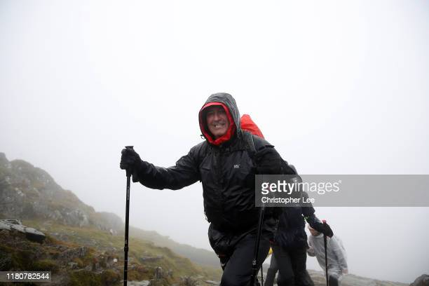 Graham Gooch smiles as he reachesa the summit of Snowdonia during the PCA Three Peaks Challenge on October 13, 2019 in Snowdonian National Park,...