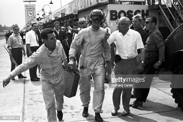 Graham Hill, 1000 Km of Nürburgring, Nurburgring, 31 May 1964. Graham Hill helping his mechanic to carry a jerrican of petrol.
