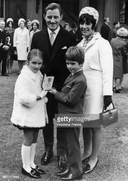 Graham Hill, entouré de ses enfants Brigitte Hill et Damon Hill et de sa femme Bette Hill, a été décoré de l'ordre de l'Empire britannique au palais...