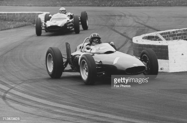 Graham Hill of Great Britain driving the Owen Racing Organisation BRM P57 V8 leads Bruce McLaren in the Cooper-Climax T55 through the chicane during...
