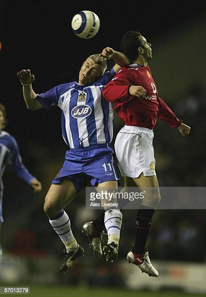 Graham Kavanagh of Wigan Athletic challenges Ryan Giggs of Manchester United during the Barclays Premiership match between Wigan Athletic and...