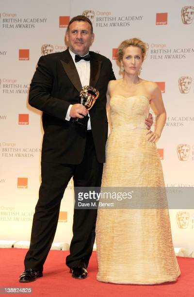 Graham King accepting the Best Animated Film award on behalf of Gore Verbinski for Rango poses with presenter Gillian Anderson in the press room at...