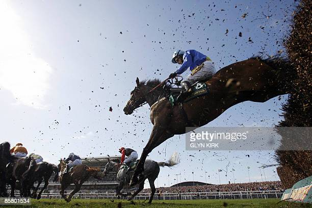 Graham Lee rides THREE MIRRORS over the last fence during the John Smith's Maghull Novices' Steeple Chase on the third day of the Grand National...