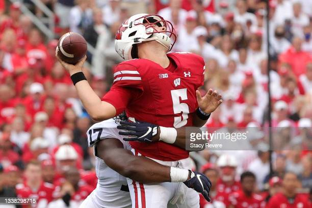 Graham Mertz of the Wisconsin Badgers is hit by Arnold Ebiketie of the Penn State Nittany Lions during the first quarter at Camp Randall Stadium on...