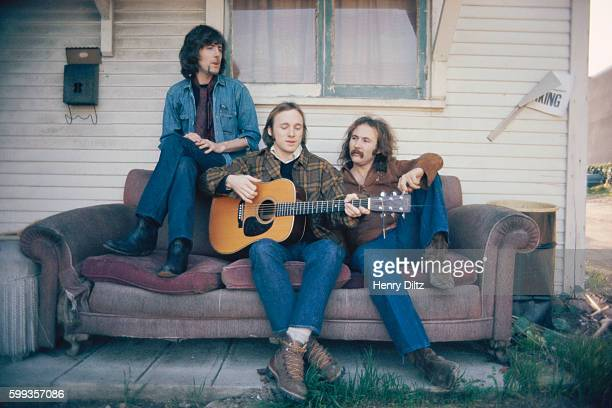 Graham Nash Stephen Stills and David Crosby relax outside on an old couch