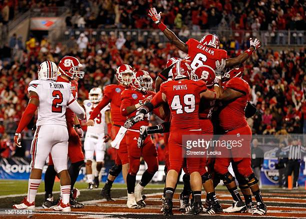 J Graham of the North Carolina State Wolfpack celebrates with teammates after scoring a touchdown against the Louisville Cardinals during their game...