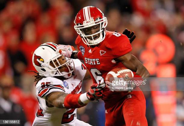 J Graham of the North Carolina State Wolfpack gets away from Anthony Branch of the Louisville Cardinals on his way to scoring a touchdown during...