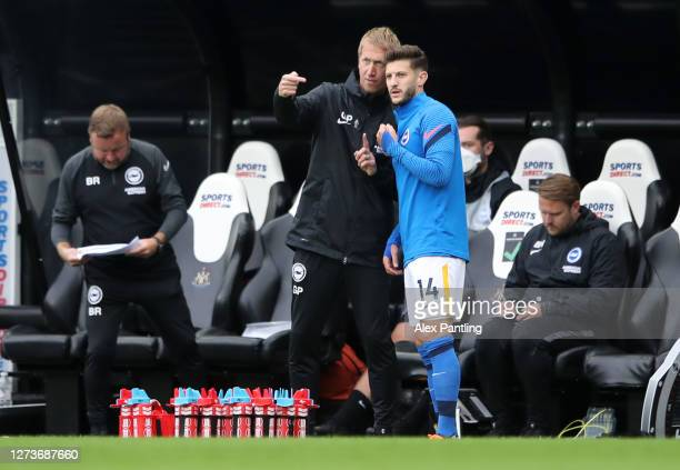 Graham Potter Head Coach of Brighton and Hove Albion speaks with Adam Lallana of Brighton and Hove Albion during the Premier League match between...