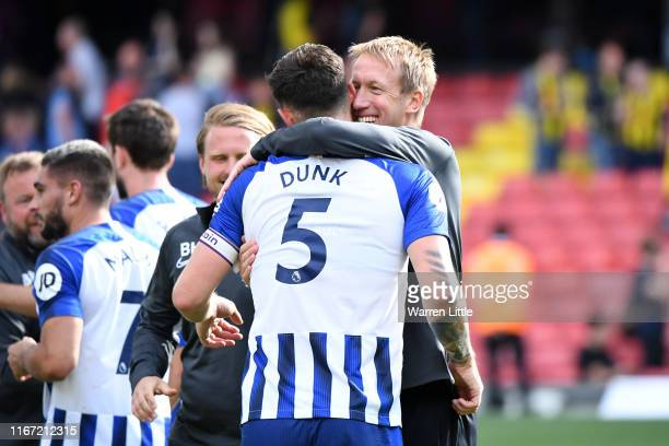 Graham Potter Manager of Brighton and Hove Albion embraces Lewis Dunk of Brighton and Hove Albion following the Premier League match between Watford...