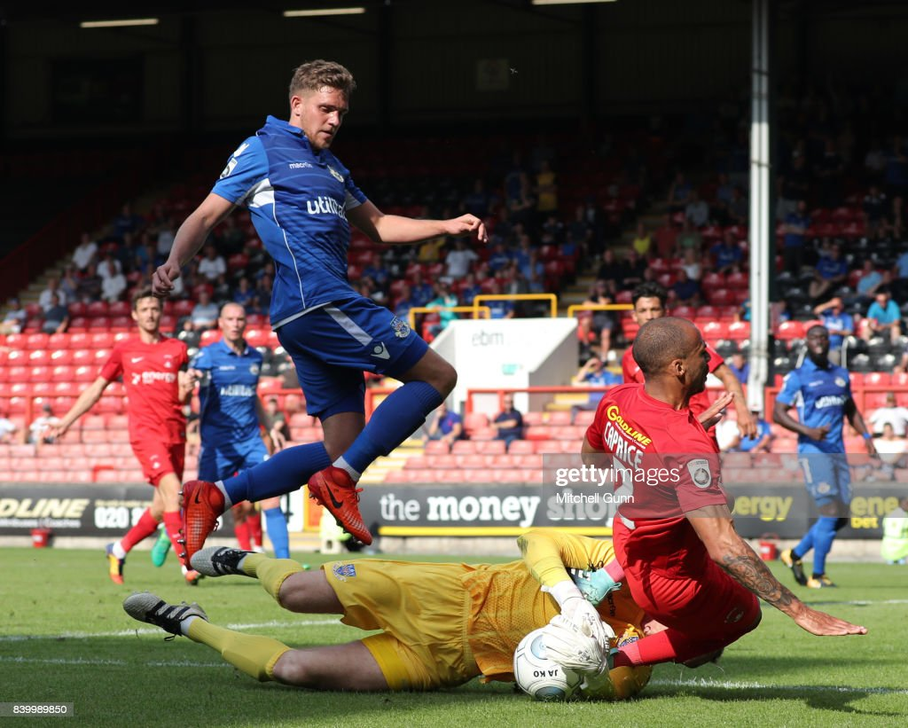 Graham Stack of Eastleigh dives at the feet of Jake Caprice of Leyton Orient during the National League match between Leyton Orient and Eastleigh at The Matchroom Stadium on August 26, 2017 in London, United Kingdom.