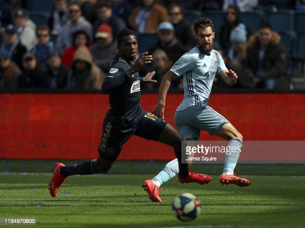 Graham Zusi of Sporting Kansas City and Cory Burke of Philadelphia Union chase the ball during the game at Children's Mercy Park on March 10, 2019 in...