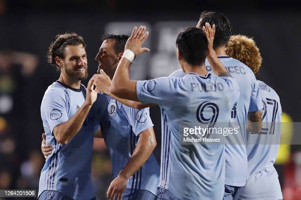 Graham Zusi of Sporting Kansas City celebrates with teammates after scoring a goal in the 91' against the Colorado Rapids during a Group D match as...
