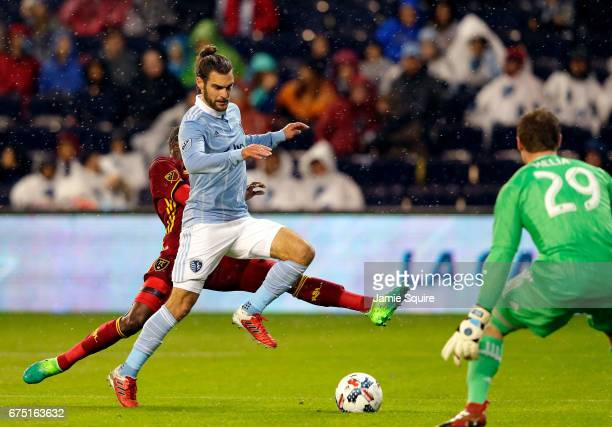 Graham Zusi of Sporting Kansas City defends against a shot on goal by Demar Phillips of Real Salt Lake as goalkeeper Tim Melia looks on during the...