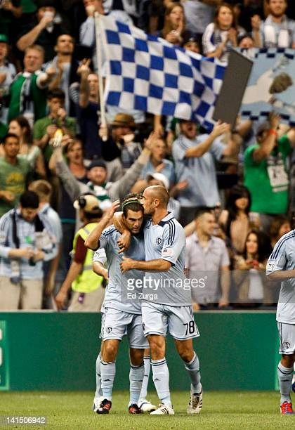 Graham Zusi of Sporting Kansas City receives a kiss on the head from Aurelien Collin after scoring in the first half against the New England...