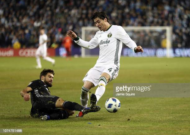Graham Zusi of Sporting Kansas City slides as Jorge Villafana of Portland Timbers controls the ball during leg 2 pf the Conference Championship at...