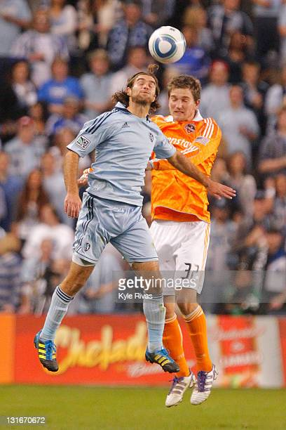 Graham Zusi of the Sporting Kansas City and Bobby Boswell of the Houston Dynamo attempt to gain control of a header in the first half during the MLS...