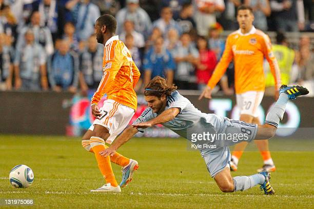 Graham Zusi of the Sporting Kansas City trips while defending Luiz Camargo of the Houston Dynamo in the second half during the MLS Eastern Conference...