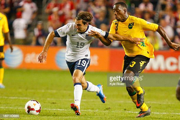 Graham Zusi of the US Men's National Soccer Team fends off Lloyd Doyley of the Jamaica late in the second half at Sporting Park on October 11 2013 in...