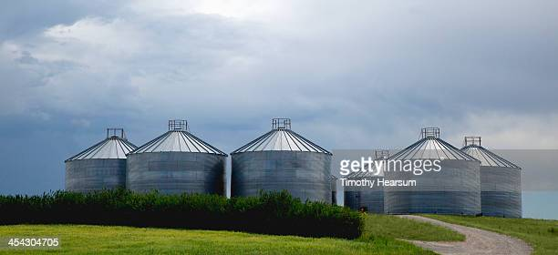 grain bins with stormy sky beyond - timothy hearsum stock pictures, royalty-free photos & images