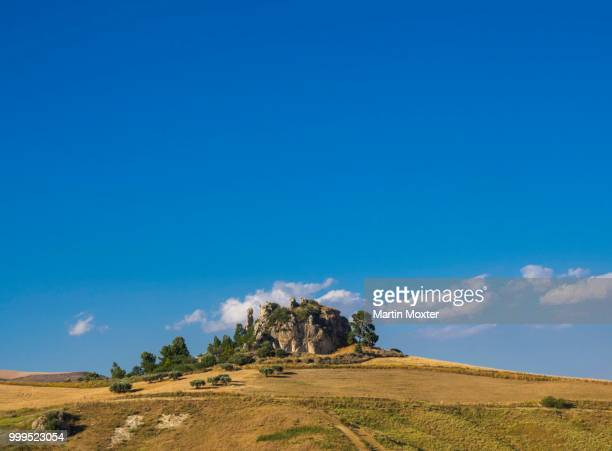 grain fields with stone formation in caltanissetta, sicily, italy - province of caltanissetta stock photos and pictures