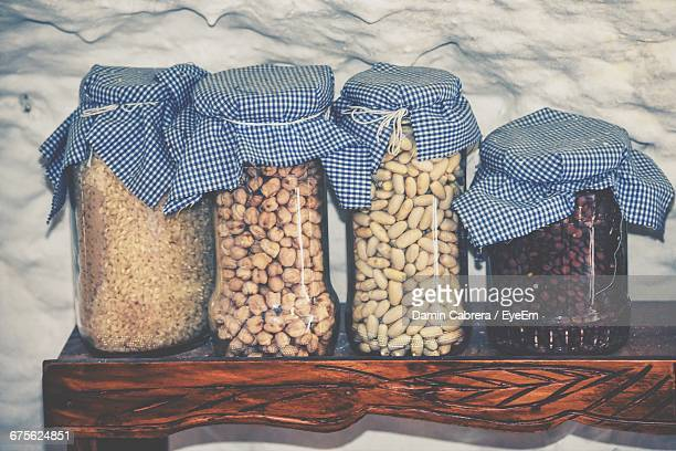 Grains In Glass Jars On Table By Wall