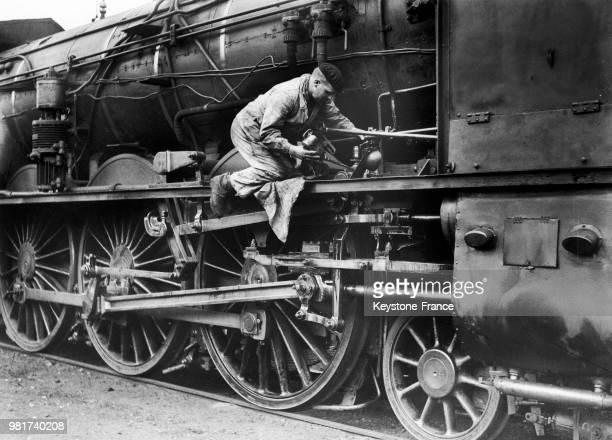 Graissage des roues, pistons et bielles d'une locomotive à vapeur de la compagnie du chemin de fer Paris-Lyon-Méditerranée , en France, en 1938.