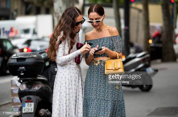 Géraldine Boublil is seen wearing grey off shoulder dress yellow bag Erika Boldrin on their smartphone outside Schiaparelli during Paris Fashion Week...